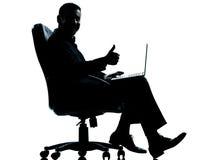 Um polegar do computador do homem de negócio que senta-se acima Fotografia de Stock Royalty Free