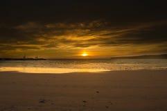 Um por do sol alaranjado em uma praia nas ilhas de Orkney imagem de stock