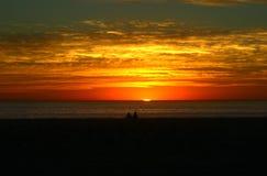 Um por do sol de observação dos pares na praia Fotos de Stock Royalty Free