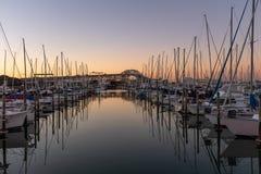 Um por do sol disparado de um porto com a ponte do porto de Auckland no fundo imagens de stock