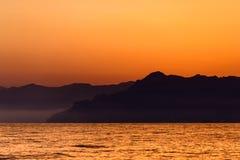 Um por do sol do mar na costa Fotografia de Stock Royalty Free