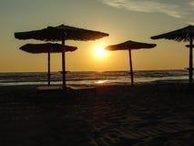 Um por do sol sob os guarda-chuvas de praia fotos de stock royalty free