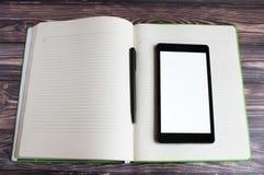 Um portátil preto encontra-se no grande caderno aberto No centro do caderno é uma pena preta para escrever imagens de stock