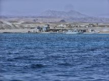 Um porto dos navios amarrados no mar ao lado de uma aldeia da montanha fotografia de stock royalty free
