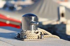 Um poste de amarração de aço inoxidável moderno com amarração na doca no porto na perspectiva dos iate em um dia ensolarado Outfi fotografia de stock royalty free