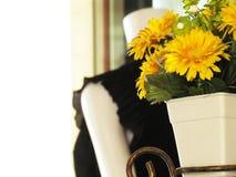 Um potenciômetro de flor artificial amarelo é colocado na tabela no núcleo Imagem de Stock Royalty Free