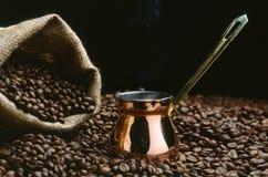 Um potenciômetro do café turco com feijões Foto de Stock