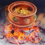 Um potenciômetro do HANDI com os carvões quentes acima ateados fogo que cozinham um guisado foto de stock