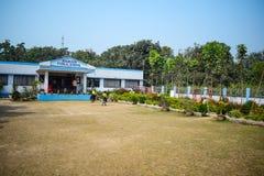 Um prédio da escola do jardim de infância com um campo de jogos na frente dele imagem de stock