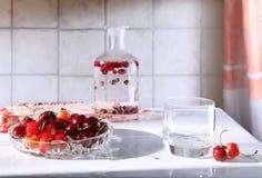 Um prato com cerejas e bebidas imagens de stock