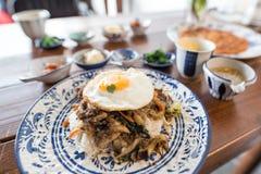 Um prato coreano coberto com ovo frito imagens de stock