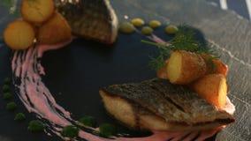 Um prato da culinária haute Close-up Peixes com batatas novas mullet Com um vidro do vinho branco Restaurante de Primorsik video estoque