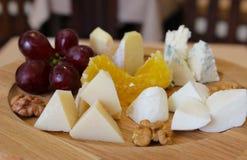Um prato de madeira com as uvas do queijo parmesão com nozes e mel fotos de stock royalty free