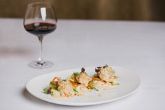 Um prato de peixes e um vidro do vinho tinto no fundo branco Foto de Stock Royalty Free