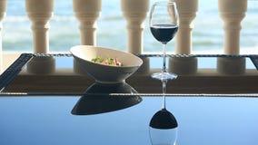 Um prato de um restaurante gourmet Close-up Carne de porco com vegetais e um vidro do vinho tinto Restaurante do beira-mar video estoque