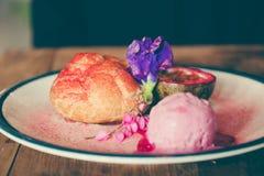 Um prato dos Choux desnata, gelado e fruto de paixão cor-de-rosa com decoração bonita imagem de stock royalty free
