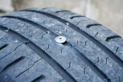 Um prego colado no pneu de carro imagem de stock