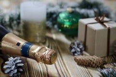 Um presente coloca em uma tabela de madeira ao lado de uma vela, dos cones e de um anjo na perspectiva das decorações do Natal foto de stock royalty free