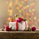 Um presente com rosas em uma tabela de madeira Cartão o 8 de março, dia do ` s da mãe Copie o espaço Imagem de Stock
