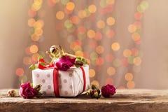 Um presente com rosas em uma tabela de madeira Cartão o 8 de março, dia do ` s da mãe Copie o espaço Fotos de Stock