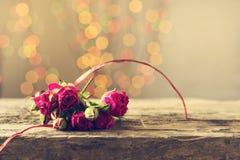 Um presente com rosas em uma tabela de madeira Cartão o 8 de março, dia do ` s da mãe Copie o espaço Fotografia de Stock Royalty Free