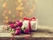 Um presente com rosas em uma tabela de madeira Cartão o 8 de março, dia do ` s da mãe Copie o espaço Imagem de Stock Royalty Free