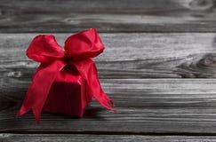 Um presente de Natal festivo vermelho no fundo gasto de madeira