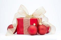 Um presente de Natal vermelho com fita do ouro e a decoração vermelha da árvore Fotos de Stock