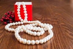 Um presente em uma caixa vermelha e em pérolas perla em um fundo de madeira fotos de stock royalty free