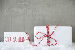 Um presente, fundo urbano do cimento, texto Gutschein significa o comprovante Imagens de Stock
