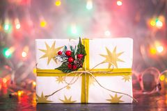 Um presente para o Natal no fundo das luzes das festões, bokeh Fotografia de Stock Royalty Free