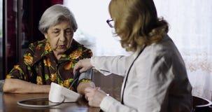 Um pressur de medição do sangue do doutor idoso de uma mulher superior dentro vídeos de arquivo