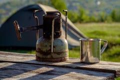Um primus soviético velho do querosene e uma caneca de aço na natureza imagem de stock