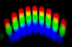 Um prisma reflete cores vibrantes em uma parede escura fotografia de stock royalty free