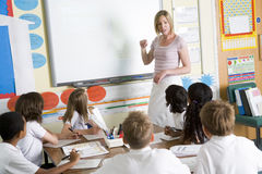 Um professor que ensina uma classe de escola júnior fotos de stock