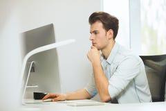 Um programador novo está olhando a câmera O designer gráfico está pensando sobre os projetos futuros O indivíduo novo imagens de stock