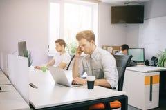 Um programador novo está olhando o computador O designer gráfico está pensando sobre os projetos futuros O indivíduo novo foto de stock royalty free