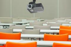 Um projetor sobre lugares vazios com tabelas em uma sala de conferências imagens de stock