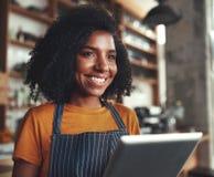 Um proprietário fêmea de sorriso do café com tabuleta digital foto de stock