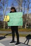 Um protestador mantém um sinal durante um março contra a brutalidade de polícia e a resolução do grande júri sobre o exemplo de E Fotos de Stock Royalty Free