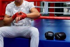 Um pugilista com as ataduras em seus braços senta-se no anel com luvas de encaixotamento fotografia de stock royalty free