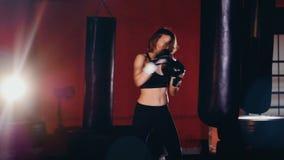 Um pugilista fêmea novo começa bater em um saco de perfuração video estoque