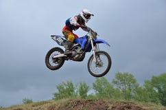 Um pulo sobre o piloto do motocross do monte Fotografia de Stock Royalty Free