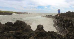 Um pulverizador de explosão de Shoots Waves Amidst do fotógrafo, Waianapanapa Imagens de Stock Royalty Free