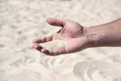 Um punhado da areia na palma humana imagem de stock