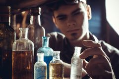 Um químico novo do cientista seleciona garrafas para a experiência imagens de stock