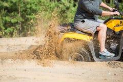 Um quadbike de ATV obtém colado em uma estrada arenosa perto da floresta e na roda-rotação ter que faz um pulverizador da areia Imagens de Stock Royalty Free