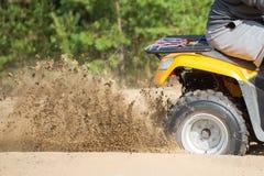Um quadbike de ATV obtém colado em uma estrada arenosa perto da floresta e na roda-rotação ter que faz um pulverizador da areia imagem de stock royalty free