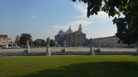Um quadrado com esculturas dos gigantes de Pádua, Itália e na parte de trás da basílica fotos de stock