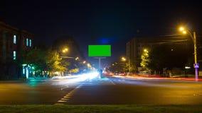 Um quadro de avisos com uma tela verde em um fundo do tráfego de cidade com exposição longa Lapso de tempo video estoque